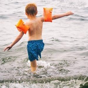 Kind met zwembandjes in de zee - sfeerfoto